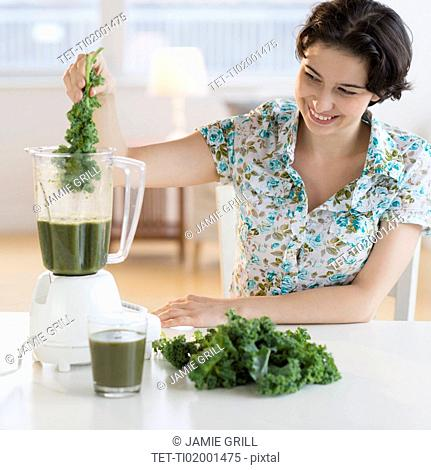 Woman preparing healthy drink with kale