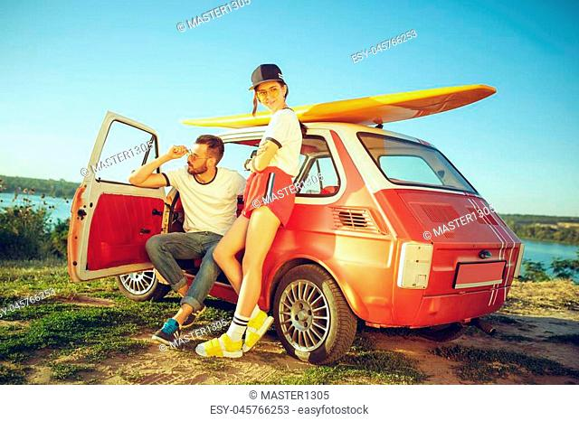 Couple resting on the beach on a summer day near river. Love, happy family, vacation, travel, summer concept. Caucasian man and woman
