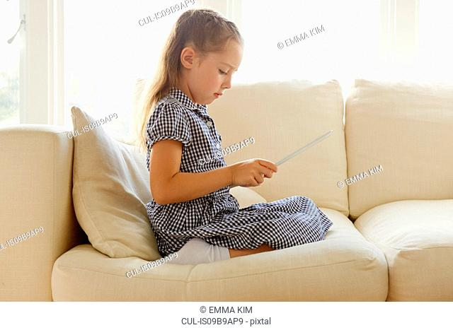 Young girl, sitting on sofa, using digital tablet