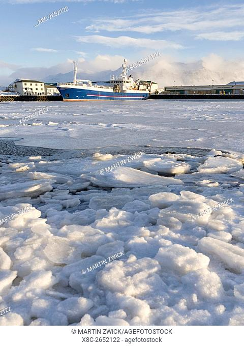 The frozen harbour of the small town Hoefn during winter. In the background the mountains of Stokksnes. europe, northern europe, iceland, February