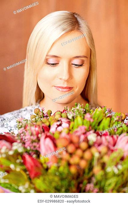 Portrait of a beautiful young woman holding flowers and looking at them