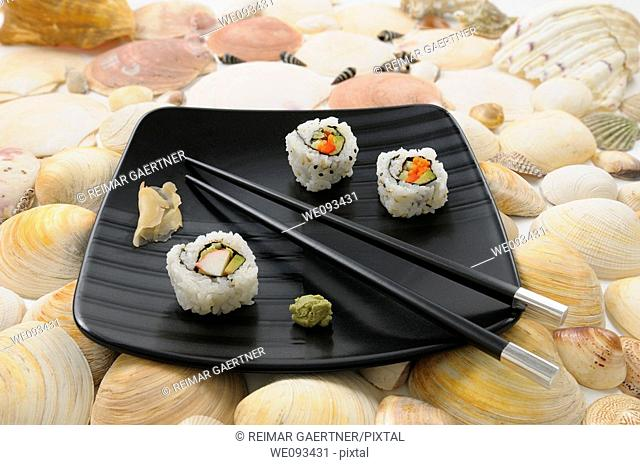 Crab Uramaki sushi and chopsticks on a black plate surrounded by sea shells