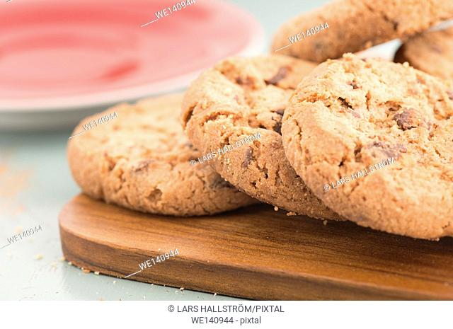 Chocolate chip cookies on wooden cutting board in close up. Sweet food, dessert or snack. The cookies are served on a kitchen table