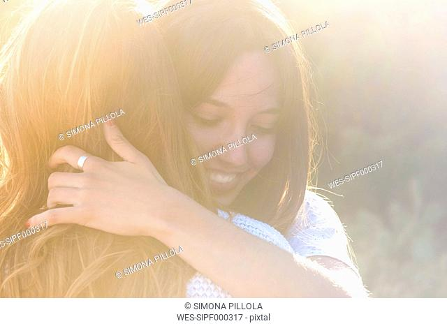 Two happy female friends hugging each other at backlight