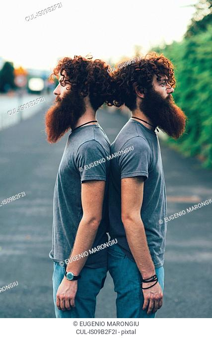 Portrait of identical adult male twins with red hair and beards back to back on sidewalk