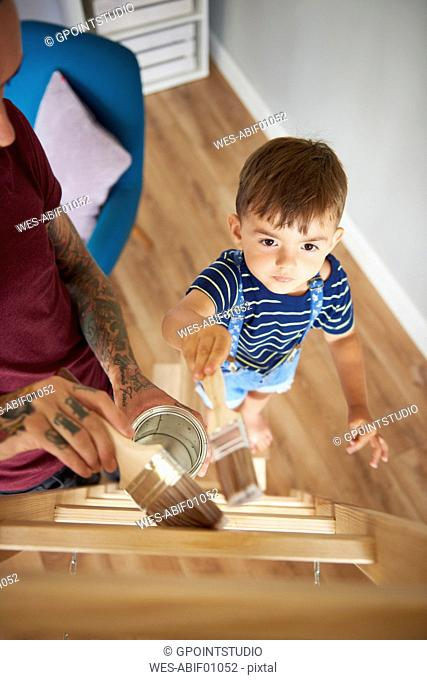 Father and son painting a ladder together at home