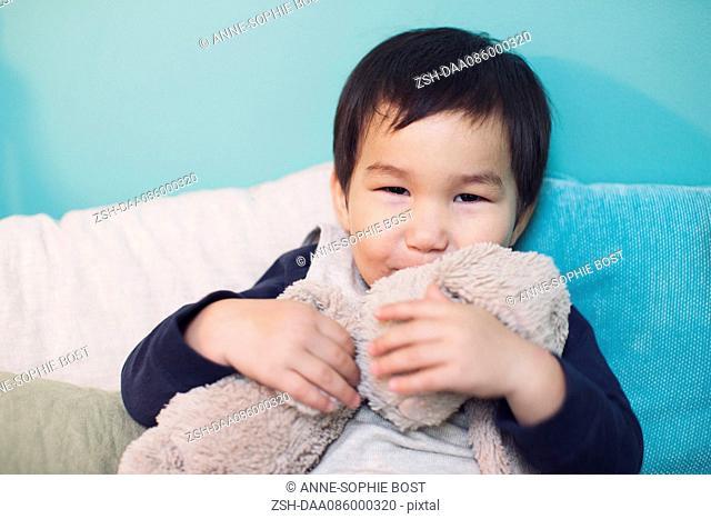 Little boy hugging stuffed toy rabbit