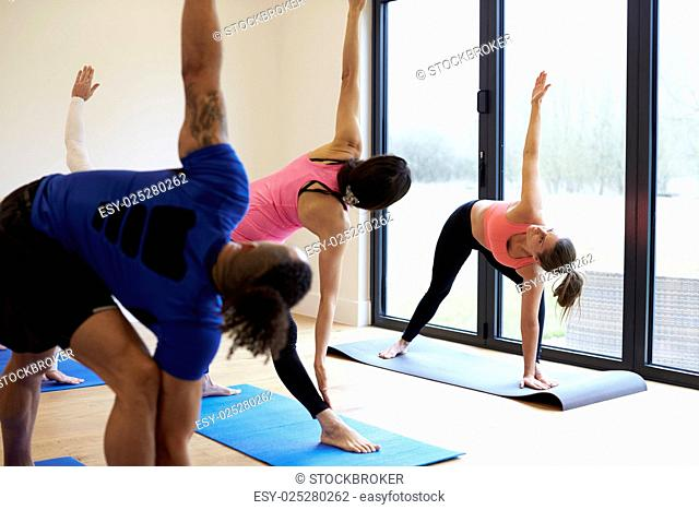 Instructor With Yoga Class At Gym