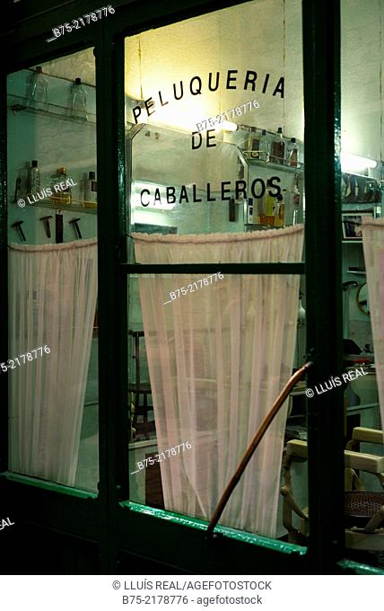 Close-up of the glass door in an old barber shop in Barcelona, Spain, Europe