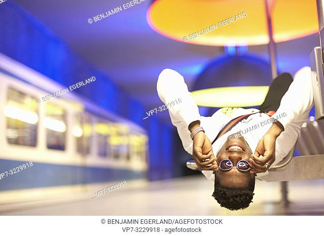 young man laying upside down on bench in underground train station, public transportation, touching sunglasses, smiling, in Munich, Germany