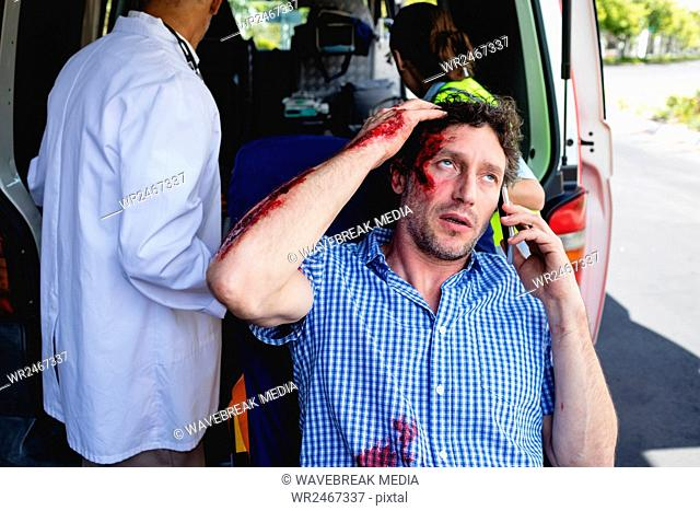 Injured man on the phone with ambulance men behind