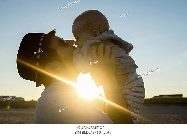 Sun beaming between Caucasian father and baby son