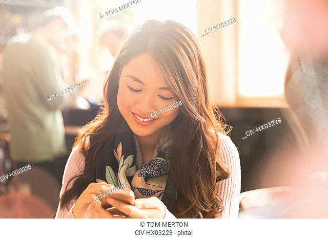 Smiling Chinese woman texting with cell phone in cafe