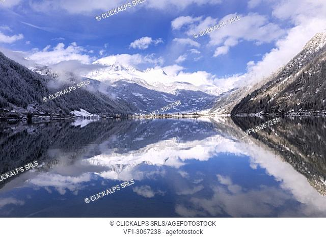 Snow-capped peacks and clouds are reflected in Poschiavo Lake. Lago di Poschiavo, Poschiavo Valley(Val Poschiavo), Graubünden, Switzerland, Europe