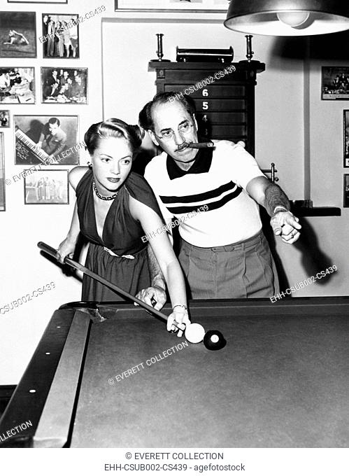 Groucho Marx at home playing billiards with his young wife, Actress Kay Maris in 1949. Her first husband was Actor Leo Gorcey, whom she married when she was 17