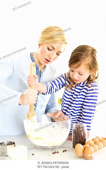 Mother and daughter (4-5) baking