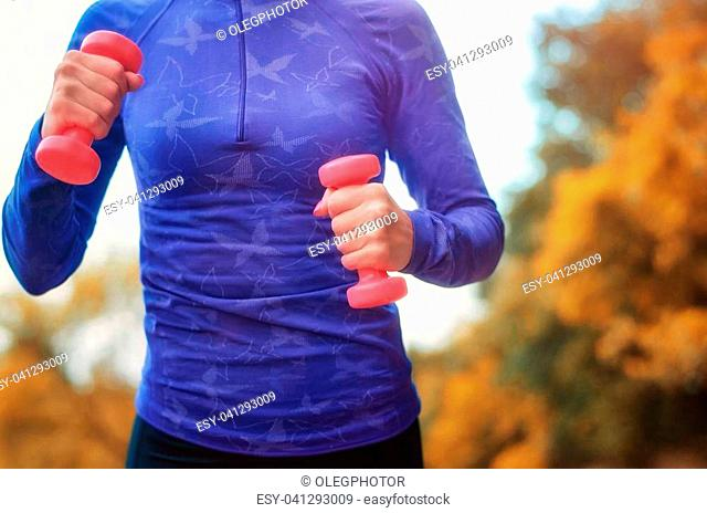 Beautiful jogger woman in blue shirt with pink dumbbells in her hands performs the sports exercise on the colorful autumn background. Shallow DOF