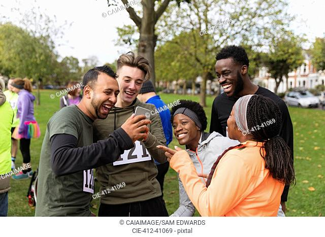 Friend runners with smart phone at charity run in park