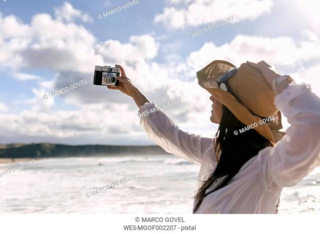 Asturias, Spain, beautiful young woman with a camera on the beach