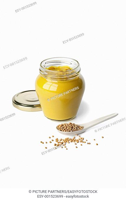 Mustard in a jar and mustard seeds on a spoon on white background