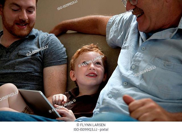 Boy showing digital tablet to grandfather