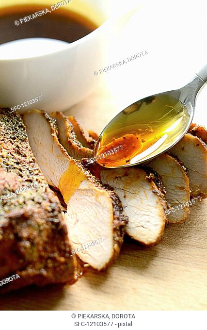 Slices of turkey breast being drizzled with gravy