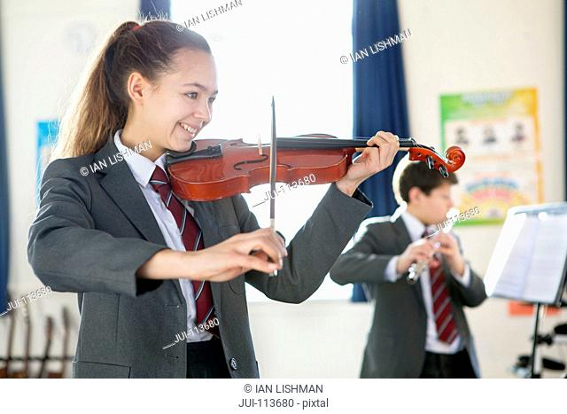 Smiling high school student playing violin in music class