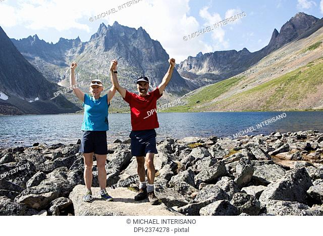 Couple posing with arms raised beside a lake in a valley with rugged mountains in the background; Yukon, Canada