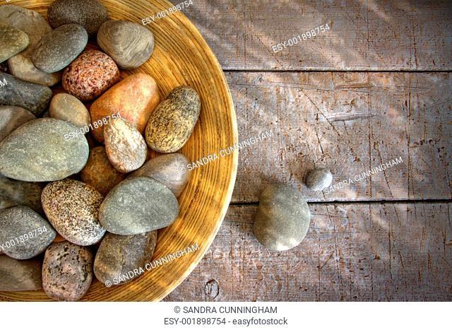 Spa rocks in wooden bowl on rustic wood