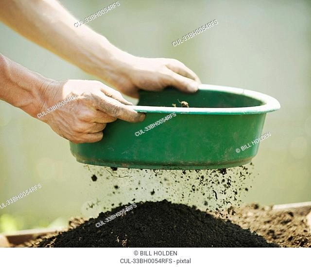 Hands sifting soil outdoors