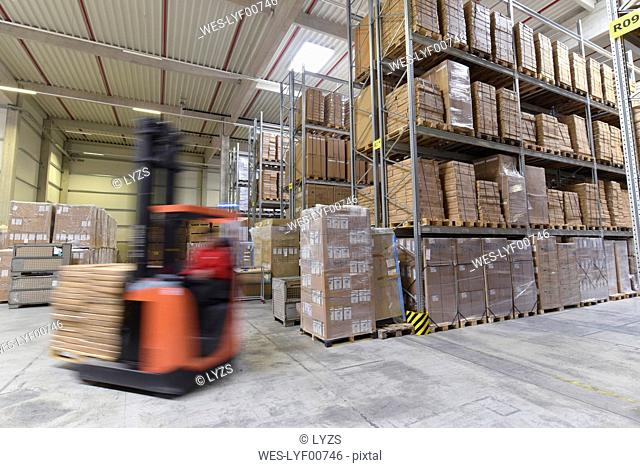 Moving forklift in factory hall