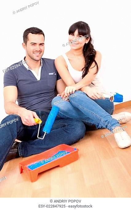Couple painting wall at home