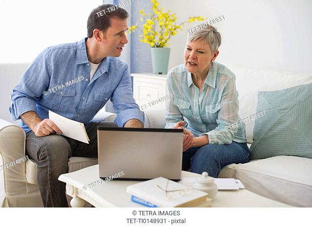 Senior mother and adult son using laptop