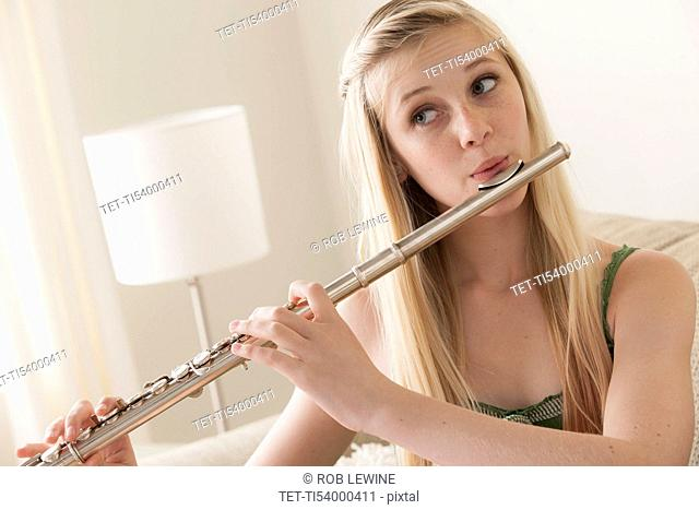Girl (14-15) playing reed flute