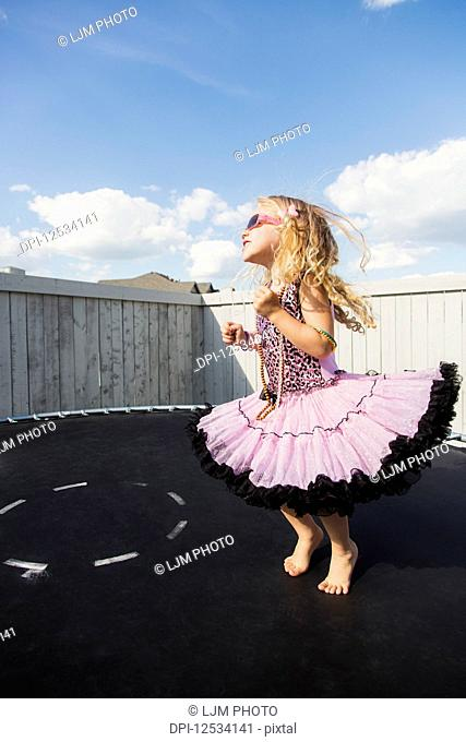 A young girl all dressed up with blond curly hair, sunglasses and jewelry standing on a trampoline in the backyard and showing off; Spruce Grove, Alberta