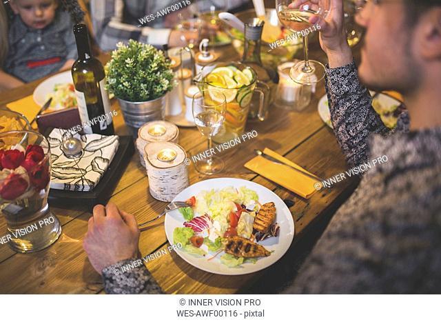 Family and friends enjoying dinner, eating, drinking, having fun