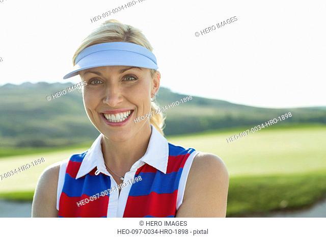 portrait of pretty, mid-adult female golfer with sun visor on