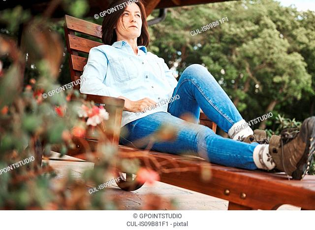 Mature woman in rural setting, relaxing on wooden lounger
