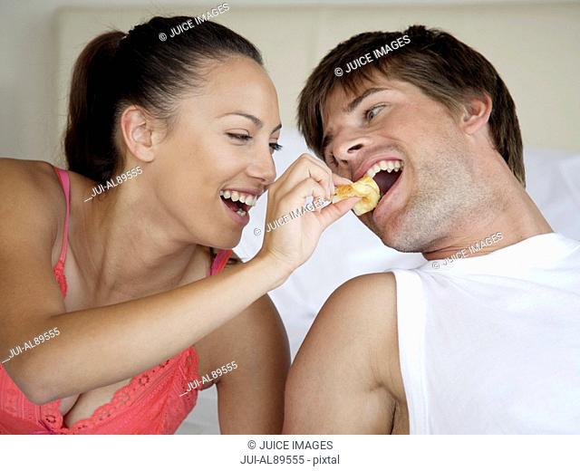 Woman feeding boyfriend in bed