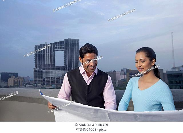 India, Architect and client looking at building plans at construction site