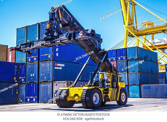 reach stacker lifting containers in a dock