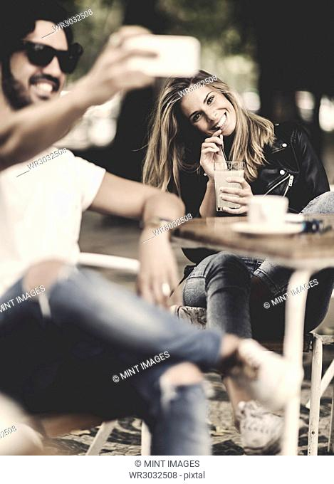 Bearded man wearing sunglasses and woman with long blond hair sitting outdoors at a table in a cafe, man holding smartphone, smiling and taking selfie