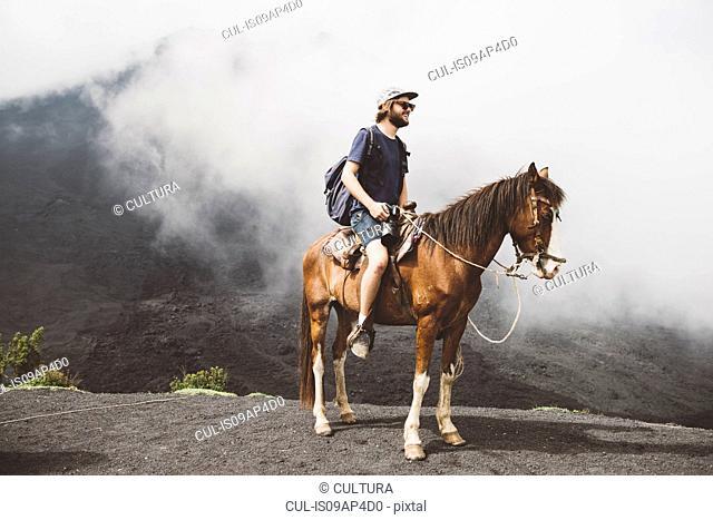 Young man horse trekking at Pacaya volcano, Antigua, Guatemala