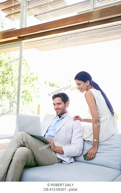 Couple using laptop on sofa