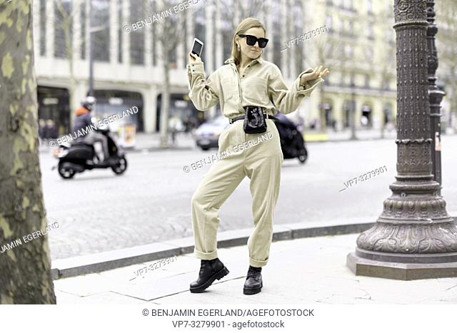 fashionable woman at street during fashion week, wearing latest fashion trend of one-piece jumpsuit, in Paris, France