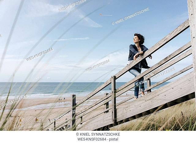 Woman standing on boardwalk at the beach