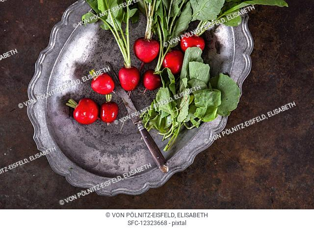 Radishes on a metal tray with a knife