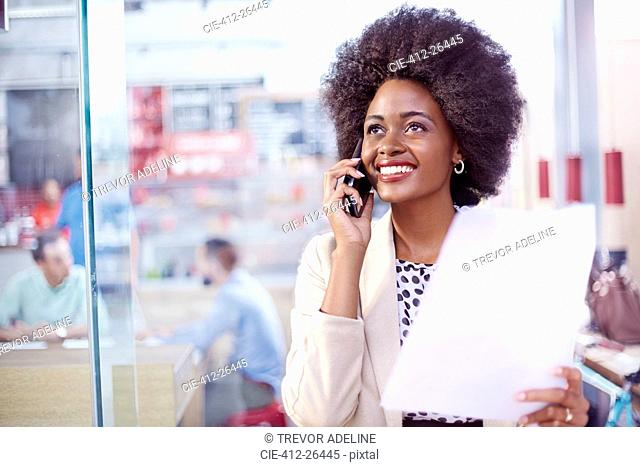 Smiling businesswoman with paperwork talking on telephone