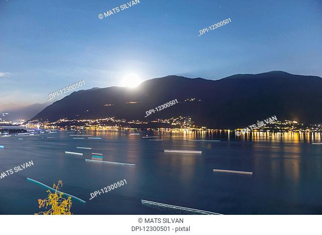 Moonlight shining over the swiss alps and Lake Maggiore; Ascona, Ticino, Switzerland