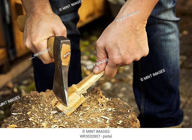 Close up of a man's hand holding an axe, cutting and shaping a small piece of wood on a splitting block covered in wood shavings